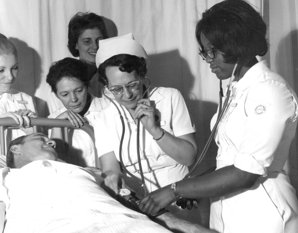 """. Practical Nurse Students to Graduate Students are members of the 112th class in licensed practical nursing to graduate from the Emily Griffith Opportunity School in 1971. Mrs. Clarice Ederer, in cap, is instructor and Theodore Wuertemburg,  is \""""patient.\""""  Others are, from left, Wendelynn Holcomb, Patricia Race, Eleanor Berg and Frances Page,  Since the program was started 20 years ago, 1,468 have graduated as practical nurses. Denver Post Library photo archive"""