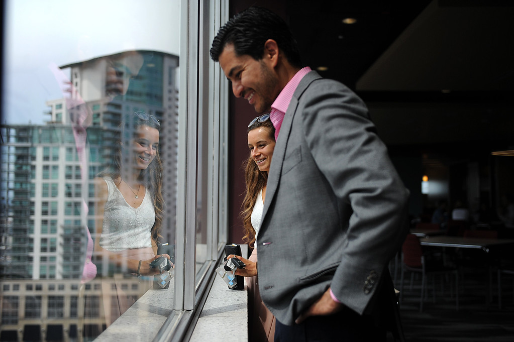 . Development Manager Ivan Anaya and Development Intern Makenna Fisher look out a window at a parking lot where a new high-rise will be built on Tuesday, August 11, 2015 in Denver. The Emily Griffith Foundation is teaming up with Zocalo Community Development to build a high-rise mixed-use building at 18th and Lincoln that will house 200 affordable apartments, as well as social enterprise businesses for Emily Griffith students, childcare and a workforce development center. (Photo by Callaghan O\'Hare/The Denver Post)