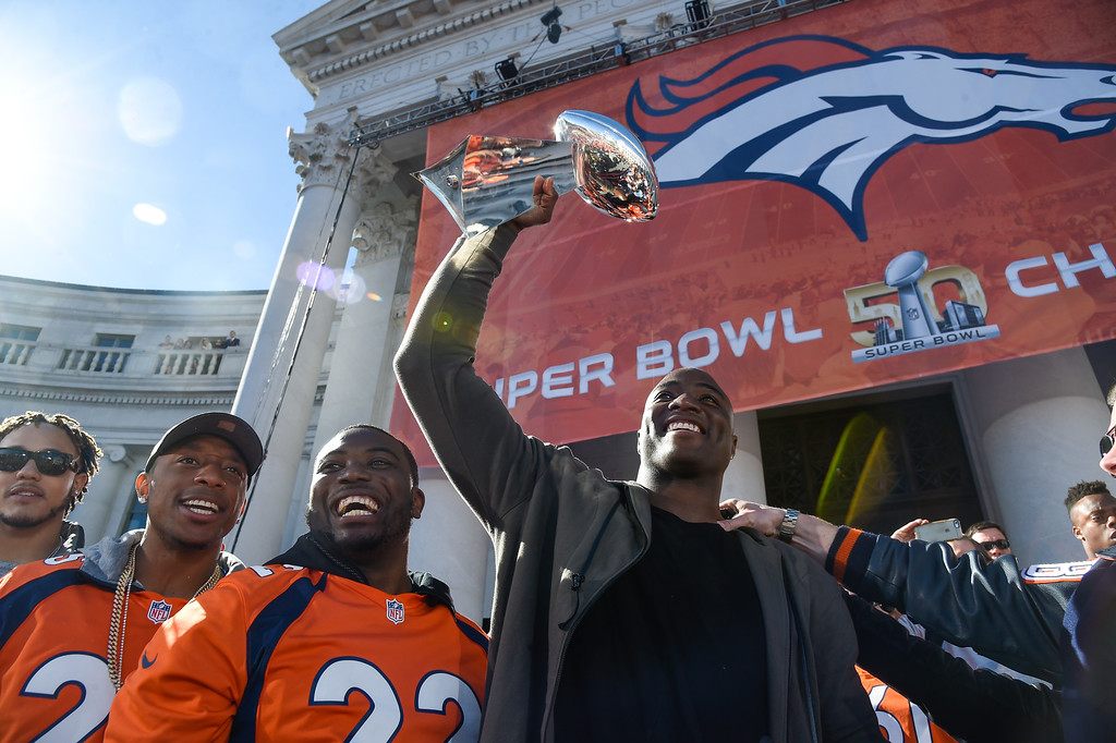 . Denver Broncos Chris Harris Jr. (25) C.J. Anderson (22) smile as DeMarcus Ware holds up the Super Bowl trophy to the crowd on the stage during the celebration.  The Denver Broncos celebrated their Super Bowl victory with a  a parade and celebration February 9, 2016 at the City & County Building. (Photo By John Leyba/The Denver Post)