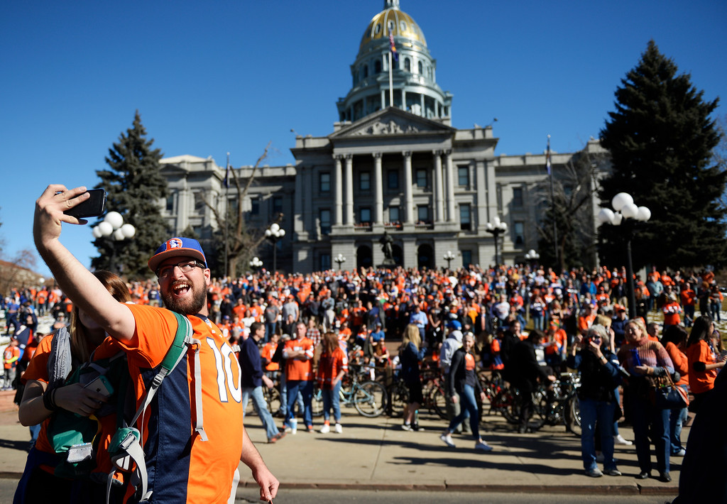 . The Denver Broncos were celebrating their Super Bowl victory with a parade through the streets of Denver on Tuesday, February 09, 2016. At the capitol Zach Canady of Parker takes a selfie with his wife Chelsea, and  daughter Reagan. (Photo by Cyrus McCrimmon/ The Denver Post)