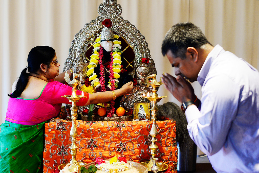. Sri Bibi, left, touches the figure of Sai Baba, that is being replaces with a permanent one at the Shri Shirdi Saibaba Temple of Rockies on February 27, 2016 in Centennial, Colorado. The worshippers of the temple held a havan, which is a fire ritual where they make offerings, to provide energy to bring to life their permanent statue of Sai Baba. Outside of the havan, they made offerings to take the figure through a purification ritual before setting it in it\'s permanent place Sunday.  (Photo by Brent Lewis/The Denver Post)