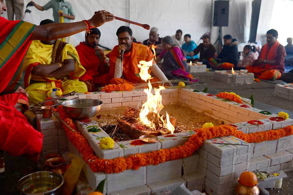 . Oil is poured into the fire at the center of the havan during a ceremony at the Shri Shirdi Saibaba Temple of Rockies on February 27, 2016 in Centennial, Colorado. The worshippers of the temple held a havan, which is a fire ritual where they make offerings, to provide energy to bring to life their permanent statue of Sai Baba. Outside of the havan, they made offerings to take the figure through a purification ritual before setting it in it\'s permanent place Sunday.  (Photo by Brent Lewis/The Denver Post)