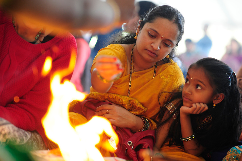 . Shilpa Polakam makes sacrifices while her daughter, Sarayu, 8, watches on during a havan at the Shri Shirdi Saibaba Temple of Rockies on February 27, 2016 in Centennial, Colorado. The worshippers of the temple held a havan, which is a fire ritual where they make offerings, to provide energy to bring to life their permanent statue of Sai Baba. Outside of the havan, they made offerings to take the figure through a purification ritual before setting it in it\'s permanent place Sunday.  (Photo by Brent Lewis/The Denver Post)