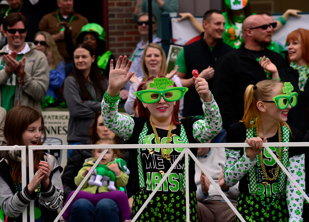. Nautica Thibodeaux, 11, right, and Kahlan Barton, 12, wear matching green glasses as they watch the 2016 Denver St. Patrick\'s Day Parade make its way down Blake Street in downtown Denver on Saturday, March 12, 2016. (Photo by Kathryn Scott Osler/The Denver Post)