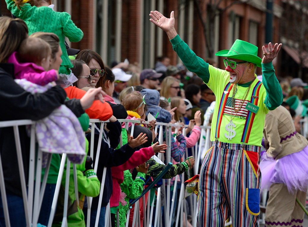 """. \""""Bucko\"""" and other members of the Colorado Clowns wave to the crowds as the 2016 Denver St. Patrick\'s Day Parade makes its way down Blake Street in downtown Denver on Saturday, March 12, 2016. (Photo by Kathryn Scott Osler/The Denver Post)"""