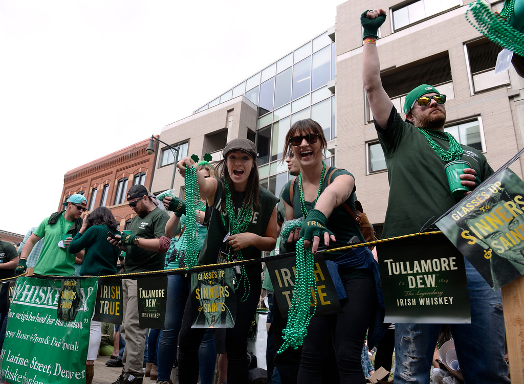 . Crews from the Whiskey Bar pass out green beads to the crowds as the 2016 Denver St. Patrick\'s Day Parade makes its way down Blake Street in downtown Denver on Saturday, March 12, 2016. (Photo by Kathryn Scott Osler/The Denver Post)