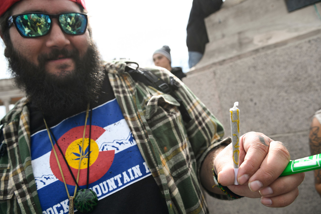 . DENVER, CO - APRIL 20: Clay Fisher 27 years old of Charleston, S.C. holds a joint with the number 420. He used a syringe with wax to apply the 420 directly on the joint.  A  big crowd gathers at Civic Center and light up during 420 celebration April 20, 2016 in Denver. (Photo By John Leyba/The Denver Post)