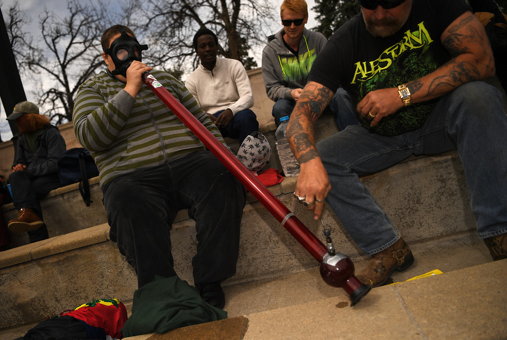 . A man smokes a home made gas mask bong as he celebrates 420 at Civic Center Park in Denver, April 20, 2016. People gather at the park to celebrate marijuana. (Photo by RJ Sangosti/The Denver Post)