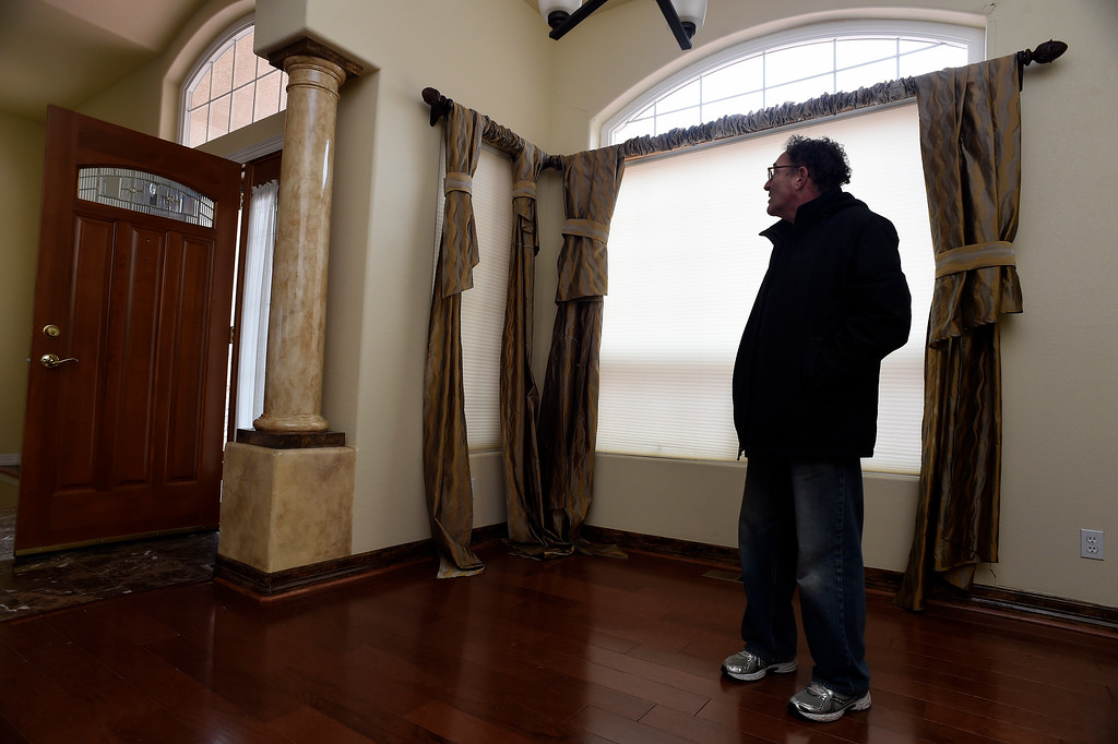 . Homeowner Jim Millman stands in the living room of his home in the  Broadmoor Bluffs on April 11, 2016 in Colorado Springs, Colorado.  The curtains all used to be uniformally off the floor but are now falling with the house. He and some of his neighbors are among 200 homeowners who have applied for federal bailouts because their home is being eaten up by collapsing expansive soil that is part of an ancient and massive landslide area.  His home was recently condemned after the moving earth finally broke the sewer and gas pipes in the house. His house has cracked walls, uneven floors and is literally sliding down the mountain.  It is a problem that city officials have known about since the mid-1990\'s when city planners approved developments on what geologists have called some of the most unstable geology on the front range.  (Photo by Helen H. Richardson/The Denver Post)