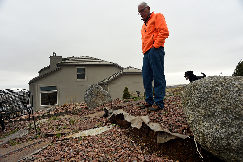 . Homeowner Denny  Cripps checks out the ever increasing crack or scarp, that is beginning to slide away from his house in Broadmoor Bluffs on April 11, 2016 in Colorado Springs, Colorado.  The Cripps are among 200 homeowners who have applied for federal bailouts because their home is being eaten up by collapsing expansive soil that is part of an ancient and massive landslide area.  Their home has cracked walls, uneven floors and is literally sliding down the mountain.  It is a problem that city officials have known about since the mid-1990\'s when city planners approved developments on what geologists have called some of the most unstable geology on the front range.  (Photo by Helen H. Richardson/The Denver Post)