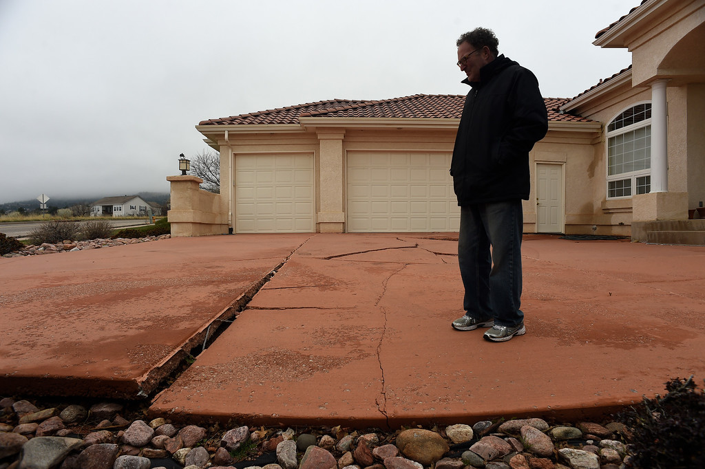 . Homeowner Jim Millman stands in his cracked driveway at his home in the  Broadmoor Bluffs on April 11, 2016 in Colorado Springs, Colorado.  He and some of his neighbors are among 200 homeowners who have applied for federal bailouts because their home is being eaten up by collapsing expansive soil that is part of an ancient and massive landslide area.  His home was recently condemned after the moving earth finally broke the sewer and gas pipes in the house. His house has cracked walls, uneven floors and is literally sliding down the mountain.  It is a problem that city officials have known about since the mid-1990\'s when city planners approved developments on what geologists have called some of the most unstable geology on the front range.  (Photo by Helen H. Richardson/The Denver Post)
