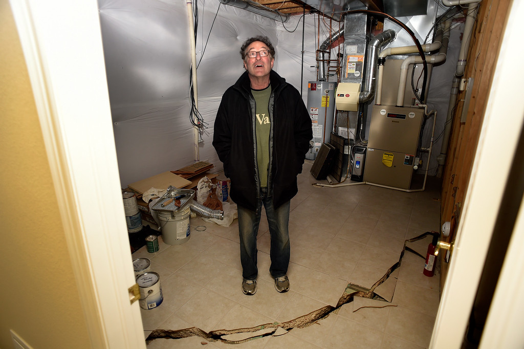 . Homeowner Jim Millman stands in the cracked basement at his home in the  Broadmoor Bluffs on April 11, 2016 in Colorado Springs, Colorado.  He and some of his neighbors are among 200 homeowners who have applied for federal bailouts because their home is being eaten up by collapsing expansive soil that is part of an ancient and massive landslide area.  His home was recently condemned after the moving earth finally broke the sewer and gas pipes in the house. His house has cracked walls, uneven floors and is literally sliding down the mountain.  It is a problem that city officials have known about since the mid-1990\'s when city planners approved developments on what geologists have called some of the most unstable geology on the front range.  (Photo by Helen H. Richardson/The Denver Post)