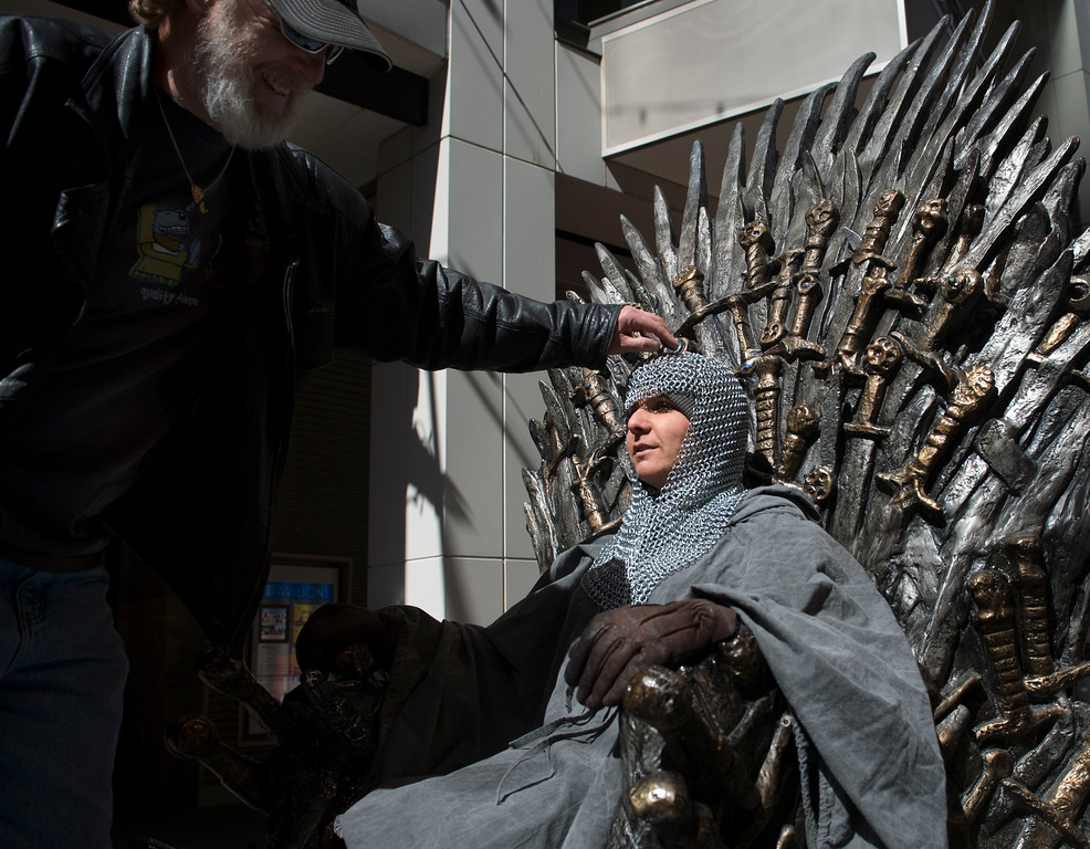 """. DENVER, CO - APRIL 22: Rick Lusk, left, poses wife Gayle Bickley in chainmail armor to look the part for their photo session on the throne. The couple from Morrison has been binge-watching \""""Game of Thrones\"""" (three seasons in one week) to try and catch up in time for Sunday\'s season six premier. The famous seat that characters are battling for in HBO\'s smash hit \""""Game of Thrones\"""" is now on display in the Denver Pavilions in downtown Denver for fans to pose and take pictures with for free leading up to the premiere of the show\'s sixth season on Sunday. (Photo by Kathryn Scott Osler/The Denver Post)"""