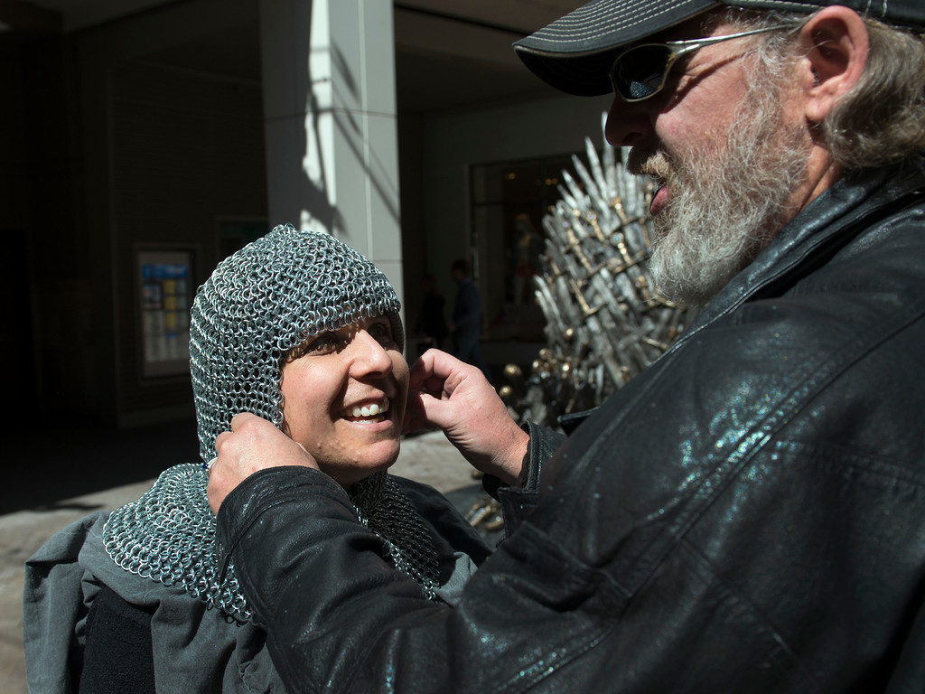 """. DENVER, CO - APRIL 22: Rick Lusk, right, dresses wife Gayle Bickley in chainmail armor to look the part for their photo session on the throne. The couple from Morrison has been binge-watching \""""Game of Thrones\"""" (three seasons in one week) to try and catch up in time for Sunday\'s season six premier. The famous seat that characters are battling for in HBO\'s smash hit \""""Game of Thrones\"""" is now on display in the Denver Pavilions in downtown Denver for fans to pose and take pictures with for free leading up to the premiere of the show\'s sixth season on Sunday. (Photo by Kathryn Scott Osler/The Denver Post)"""