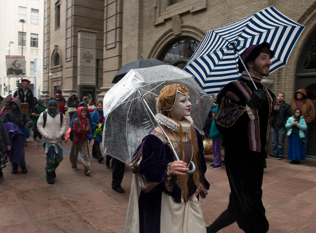 . The King and Queen of England, Vicky Serdyuk, left, and Michael Berger, use their umbrellas to try and keep dry as they lead the parade. (Photo by Kathryn Scott Osler/The Denver Post)