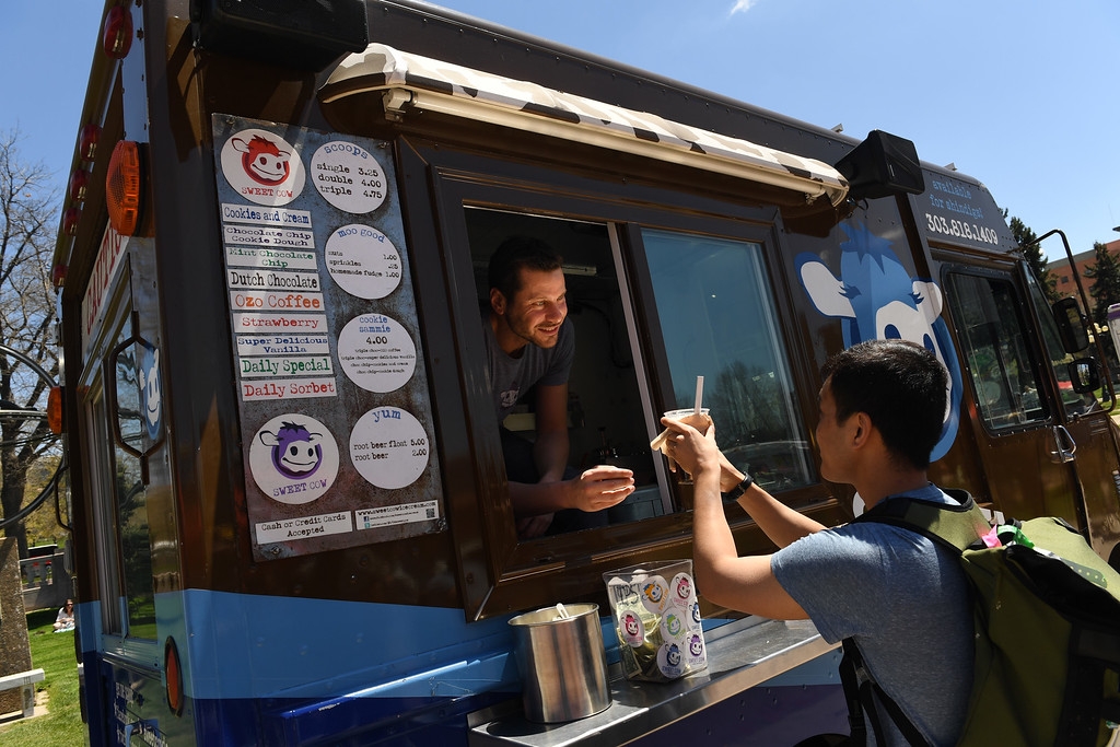 . Ross Cohen, left, owner of Sweet Cow Ice Cream truck, gives a delicious cup of homemade ice cream to a customer  at Civic Center Park on the first day of the 11th annual Civic Center EATS on May 3, 2016 in Denver, Colorado.  (Photo by Helen H. Richardson/The Denver Post)