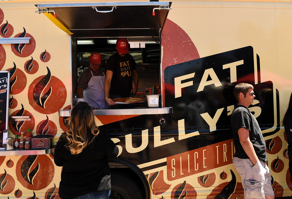 . James Tomasi, left, and Sebastian Duffell, middle in side truck, serve a large pizza to customers at their Fat Sully\'s Slice Truck at Civic Center Park on the first day of the 11th annual Civic Center EATS on May 3, 2016 in Denver, Colorado.  (Photo by Helen H. Richardson/The Denver Post)