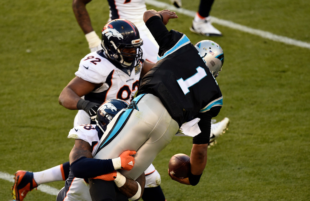 . Cam Newton (1) of the Carolina Panthers gains a first down in the second quarter as he is hit by Von Miller (58) of the Denver Broncos.  The Denver Broncos played the Carolina Panthers in Super Bowl 50 at Levi\'s Stadium in Santa Clara, Calif. on February 7, 2016. (Photo by John Leyba/The Denver Post)