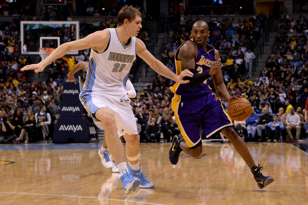 . Kobe Bryant (24) of the Los Angeles Lakers drives past Timofey Mozgov (25) of the Denver Nuggets  during the second half of the Lakers\' 111-103 win. The Denver Nuggets hosted the Los Angeles Lakers at the Pepsi Center on Monday, December 30, 2014. (Photo by AAron Ontiveroz/The Denver Post)