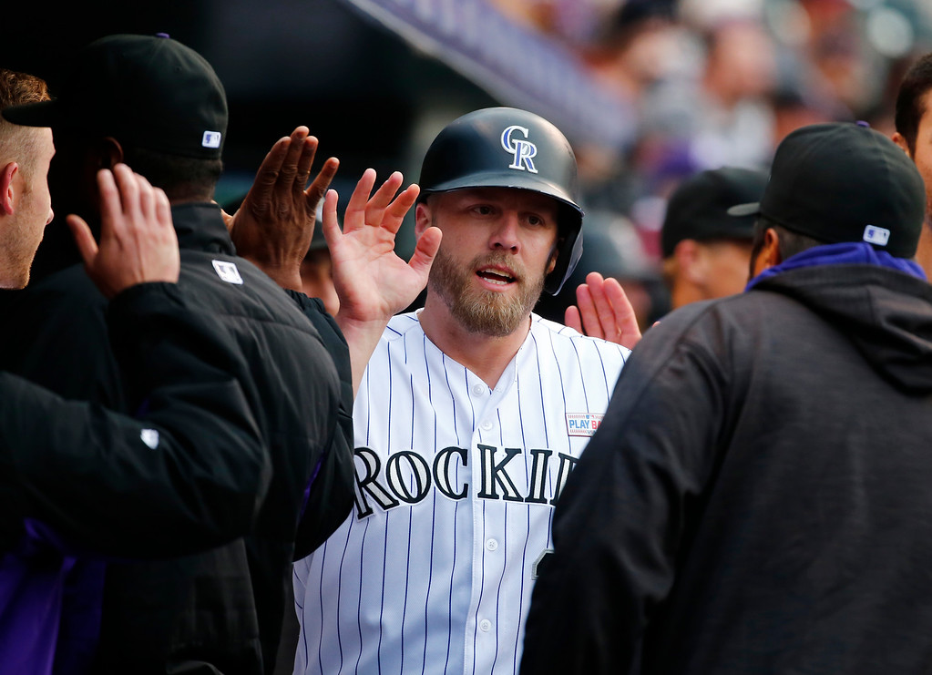 . Colorado Rockies\' Mark Reynolds is congratulated by teammates after scoring against the New York Mets during the second inning of a baseball game Saturday, May 14, 2016, in Denver. (AP Photo/Jack Dempsey)