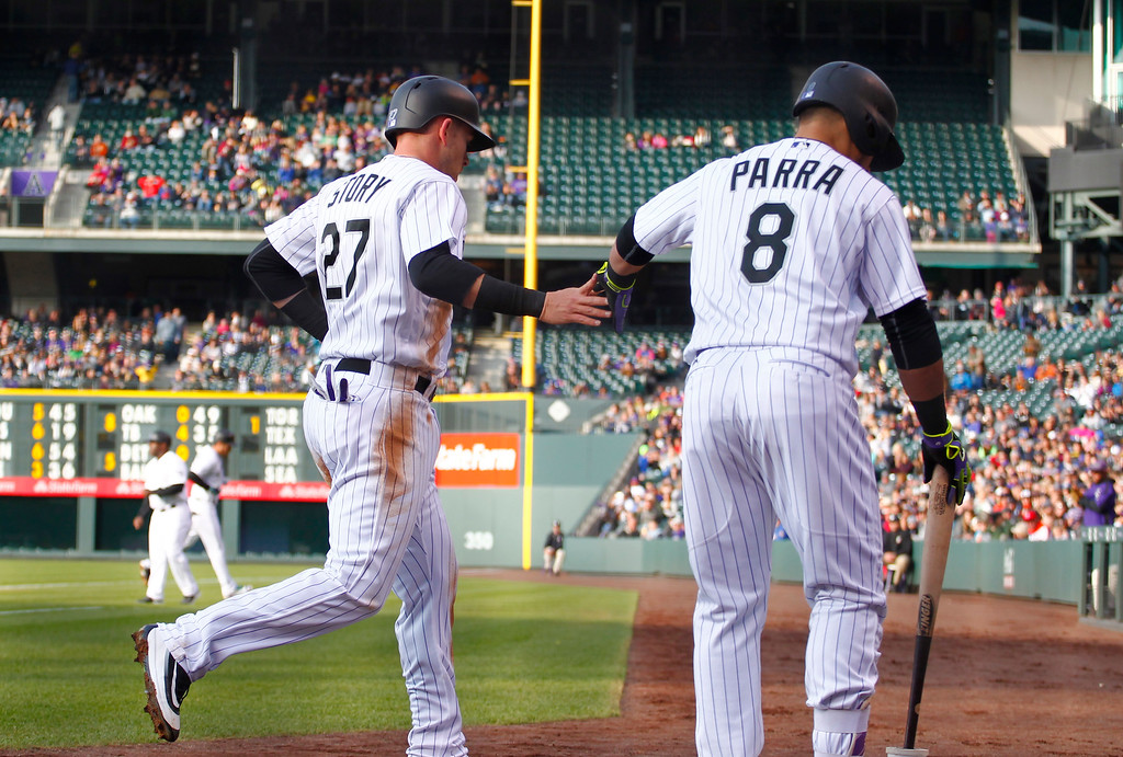 . Colorado Rockies\' Trevor Story (27) is congratulated by Gerardo Parra (8) after scoring against the New York Mets during the first inning of a baseball game Saturday, May 14, 2016, in Denver. (AP Photo/Jack Dempsey)