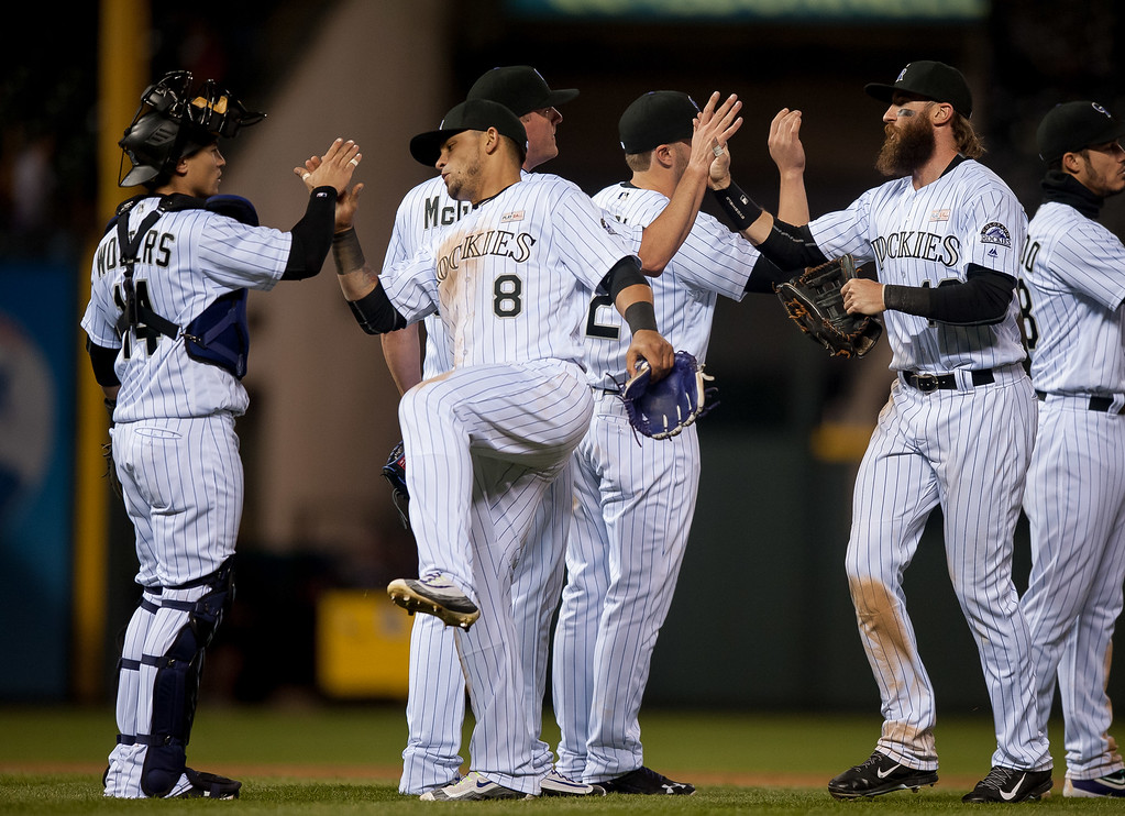 . Colorado Rockies players, including Tony Wolters #14, Gerardo Parra #8, and Charlie Blackmon #19  celebrate after a 7-4 win over the New York Mets  at Coors Field on May 14, 2016 in Denver, Colorado.  (Photo by Dustin Bradford/Getty Images)