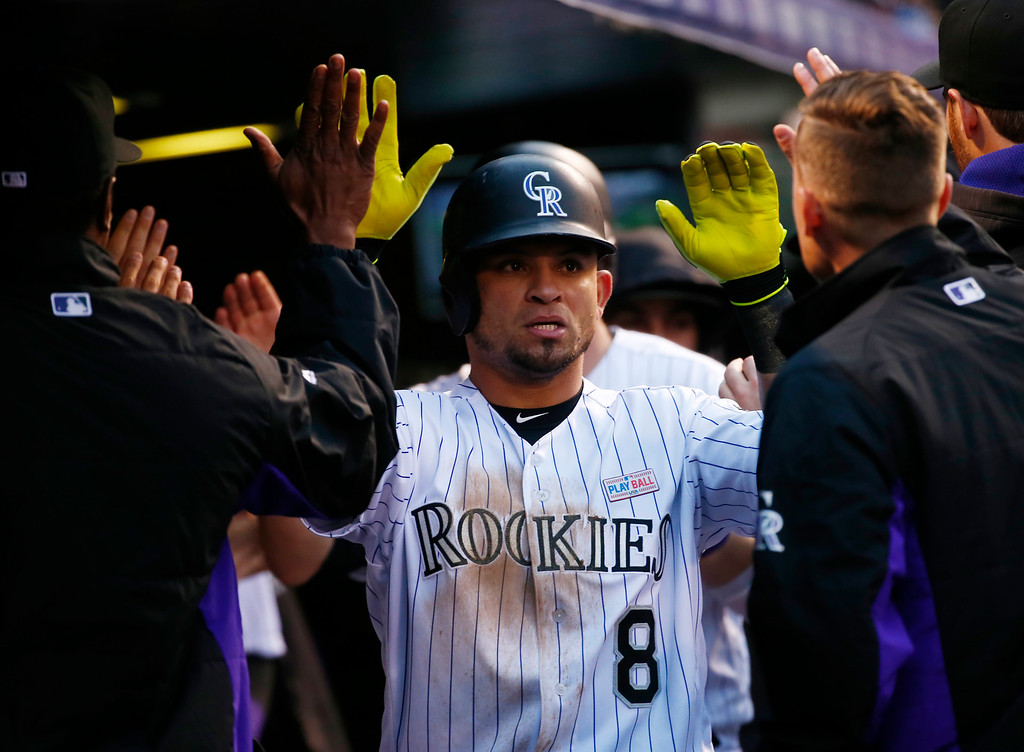 . Colorado Rockies\' Gerardo Parra is congratulated by teammates after scoring against the New York Mets during the third inning of a baseball game, Saturday, May 14, 2016, in Denver. (AP Photo/Jack Dempsey)
