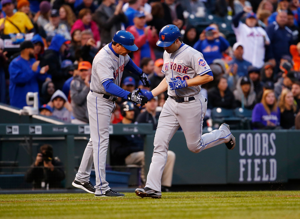 . New York Mets\' Neil Walker is congratulated by third base coach Tim Teufel after hitting a solo home run off Colorado Rockies starting pitcher Eddie Butler during the fourth inning of a baseball game, Saturday, May 14, 2016, in Denver. (AP Photo/Jack Dempsey)