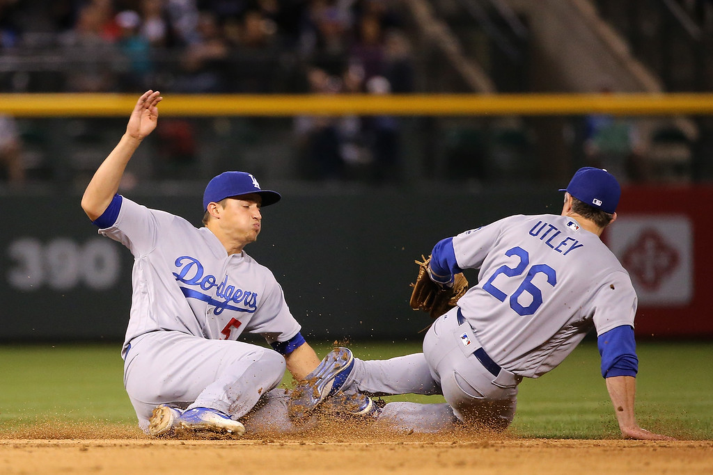 . Shortstop Corey Seager #5 of the Los Angeles Dodgers makes the stop on a ground ball by Carlos Gonzalez #5 of the Colorado Rockies and collides with second baseman Chase Utley #26 of the Los Angeles Dodgers as Gonzalez singles in the sixth inning at Coors Field on April 23, 2016 in Denver, Colorado  (Photo by Doug Pensinger/Getty Images)