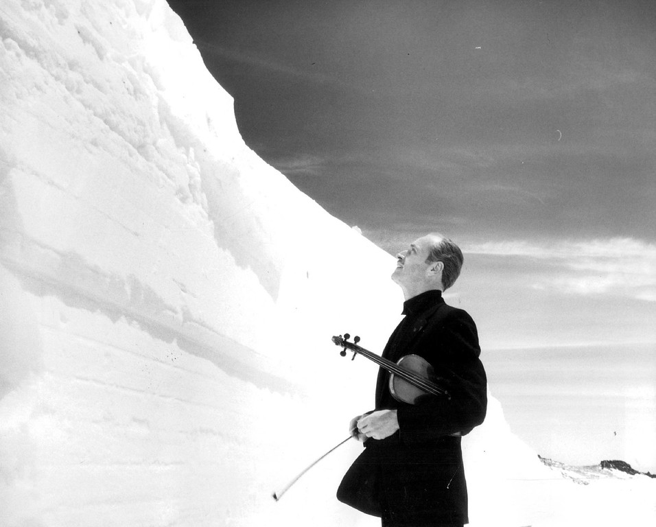 . Snow Provides Symphony of Sight Walter Charles, conductor of the Blue Jeans Philharmonic Orchestra at Estes Park, Colo., holds his $10,000 violin as he gazes at a towering snowbank on Trail Ridge Road in Rocky Mountain National Park, 1964. (Denver Post Library photo archive)