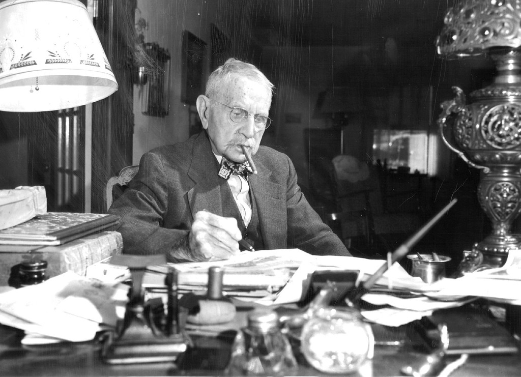 """. W.A. Colt of Lyons, Colo., celebrating his ninety-fifth birthday, \""""kind of likes a cigar\"""" and attributes his lengthy life to \""""never worrying.\"""" He was the contractor for the Trail Ridge road, and was active in business and civic affairs since retiring in 1937. (Denver Post Library photo archive)"""