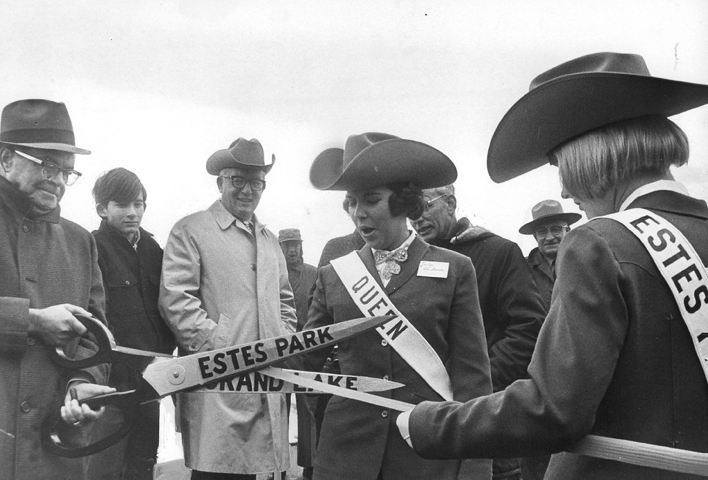 . Lou Middlemist, State Purchasing Agent, Gives Estes Park Queen Assistance In Ribbon Cutting. Queen is Jonlyn Ver Straeten of Estes Park, Colo., at right is Susie Moyers, her assistant. Behind blades, smiling, is Revill Fox, president of the Colorado Visitors Bureau, master of ceremonies at the Trail Ridge Road opening in 1966. (Ira Gay Sealy/The Denver Post)