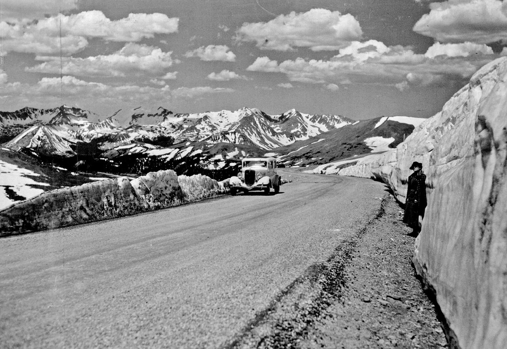 """. It\'s Ice-Cool Colorado, Up Here! This Mid-June picture in 1936 of Old Mother Nature\'s great out door air conditioning plant in Rocky Mountain National park was taken Sunday by Ralph B. Baird, Post staff photographer, near the topmost point on the world-famous Trail Ridge road, 12,183 feet--two and three-tenths miles-above sea level. The young lady beside the big snowbank is a visitor from Texas, who \""""simply wouldn\'t believe it till she saw it.\"""" The bank goes straight up twice her height, then shelves up for a maximum depth of twenty feet. The smooth government highway is open, clear and dry, from Estes Park to Grand Lake. (Denver Post Library photo archive)"""