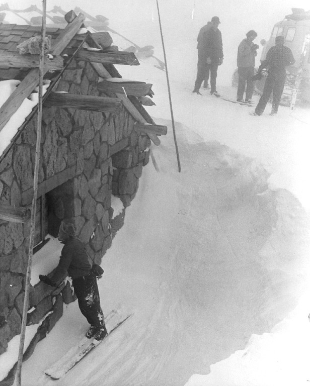 """. At Fall River Pass store and museum, Haines inspects the open side of building where snow has drifted around, leaving a large pit in 1960. Combination of fog and snow, called a \""""white-out,\"""" reduced visibility to a few feet at this stage of the Trail Ridge trip. (Denver Post Library photo archive)"""