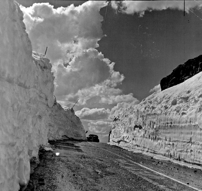 . Winter Surrenders and traffic is flowing again over the famous Trail Ridge road between Estes Park and Grand Lake, Colorado in 1942. Here, at more than 12,000 feet above the sea, Old Man Winter made his last stand of the 1942 spring campaign in Rocky Mountain National Park. The jig was up as mechanized high way monsters battered this clean-cut breach thru his lines, leaving high drifts on either side of the road. Photograph by Ralph Baird, Denver Post staff Photographer.