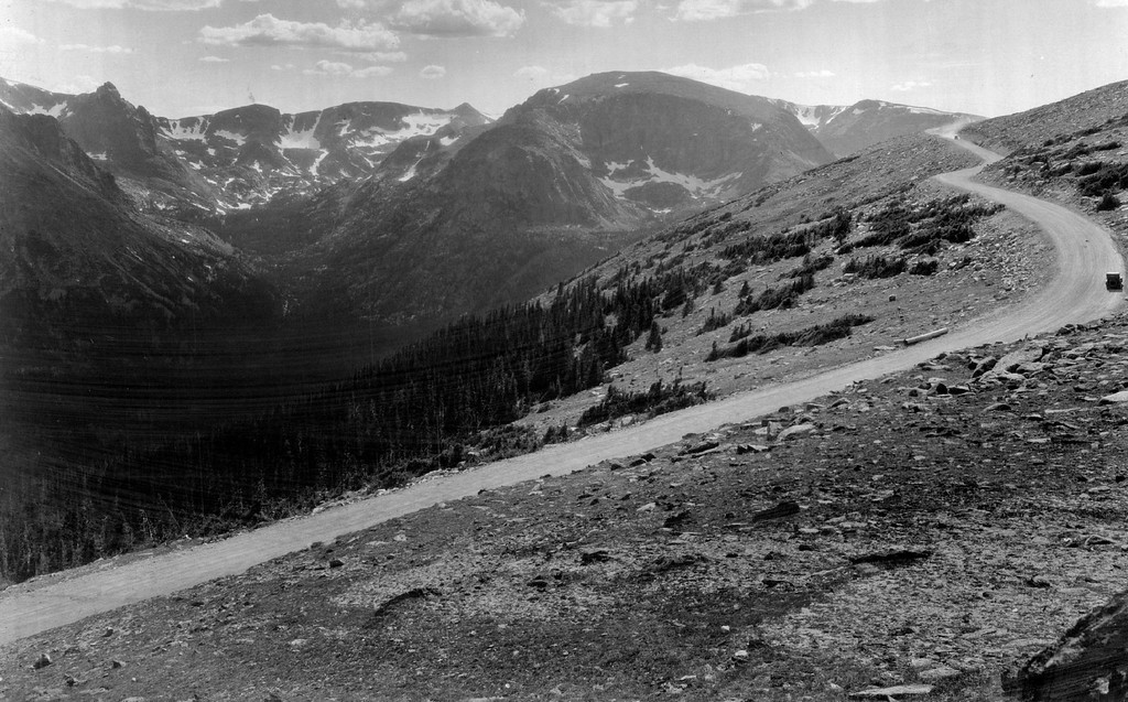 . Here is a section of the Trail Ridge road in 1935, the most magnificently scenic drive in America, that takes the awestricken traveler clear to the top of the world, over 11,000 feet high, and yet does it so gradually, so safely, that one does not realize the heights attained until he looks out over a breath-taking mountain panorama. Look at the width of this Colorado skyway. Photo by H.L. Standley.