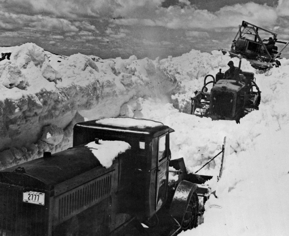 . This \'Midwinter\' Scene is, in reality, a summer picture of national park crews caught as they worked to open the famous Trail Ridge road in the Rocky Mountain national park for traffic by May 30 in 1941. Where these men are working the snow drifts were twenty feet in depth. The scene is near the Continental divide. The heavy-duty bulldozers are pushing the snow to the rotary plow in the foreground.  Credit: Associated Press Photo