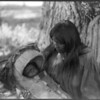 Title: Mizheh and babe.  <br /> Date Created/Published: c1906 December 19.  <br /> Summary: Apache woman, at base of tree, holding infant in cradleboard in her lap.  <br /> Photograph by Edward S. Curtis, Curtis (Edward S.) Collection, Library of Congress Prints and Photographs Division Washington, D.C.