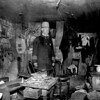 Two officials of the New York City Tenement House Department inspect a cluttered basement living room, ca. 1900. (Courtesy of the National Archives)