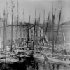 Oyster fleet in Baltimore Harbor, Md., ca. 1885. Ships' masts dominate the foreground; buildings, horse-drawn wagons, and carts visible through them. (Courtesy of the National Archives)
