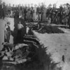 """""""Burial of the dead at the battle of Wounded Knee, S.D."""" U.S. Soldiers putting Indians in common grave; some corpses are frozen in different positions. South Dakota. c1891 Jan. 17. Northwestern Photo Co. (Trager & Kuhn) Chadron, Neb. (Library of Congress Prints and Photographs Division)"""