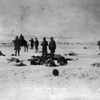 """""""Scene after the battle."""" Jan. 1891. View southwest from center of council circle after the fight at Wounded Knee Creek, Pine Ridge Reservation, South Dakota, shows men holding moccasins and other souvenirs among the frozen bodies of Native American Lakota Sioux on the snow covered ground. (Denver Public Library; Western History Collection)"""