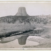 """Title: Devil's Tower. Distant view of Devils Tower and reflection of tower in stream in foreground. 1890. According to the National Park Service, over twenty tribes have potential cultural affiliation with the landmark. Among other names, The Lakota Sioux call Devils Tower """"Bear Lodge."""" Repository: Library of Congress Prints and Photographs Division Washington, D.C. 20540"""