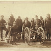 """Seven Lakota scouts and four uniformed Euro-Americans posed behind an artillery piece or Hotchkiss gun, probably in the Pine Ridge Reservation near Wounded Knee, South Dakota. """"Copr. Paul Wernert [i.e. Weinert] and gunners of Battery """"E"""" 1st Artillery / photo. and copyright 1891 by the Grabill P. & V., Deadwood, S.D."""" (Library of Congress Prints and Photographs Division)"""