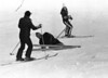 President Ford laughs as he starts to get up after a skiing spill at Vail, December 26, 1975.  In the background, U.S. Olympic slalom skier Susie Patterson smiles toward the President.  Ford was on his second run on Bwana Run, an intermediate/advanced ski run, when he fell.  Brushing off the snow, Ford continued to ski his morning run unhurt.  At left is a Secret Service agent. (AP Photo/Charlie Tasnadi)