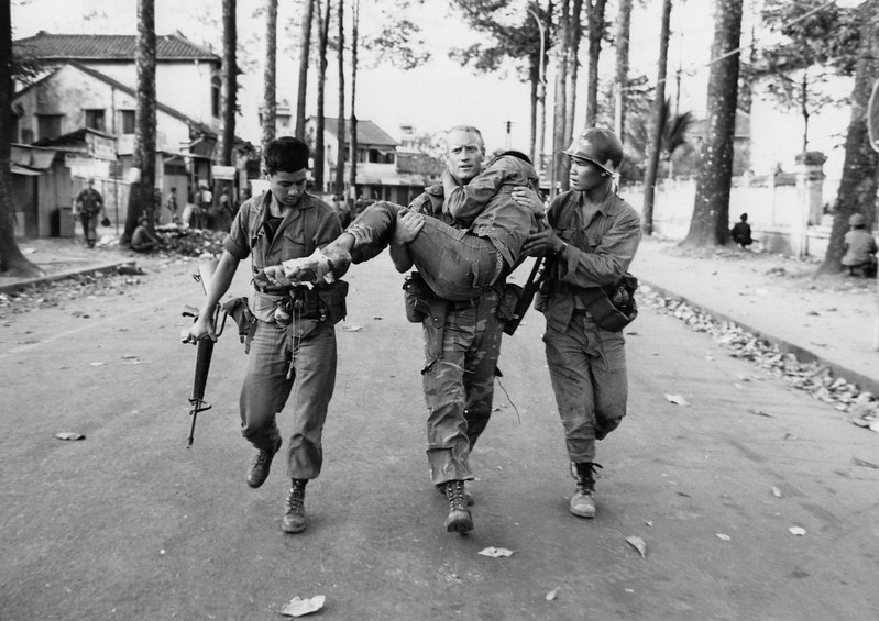 Description of  First Lt. Gary D. Jackson of Dayton, Ohio, carries a wounded South Vietnamese Ranger to an ambulance Feb. 6, 1968 after a brief but intense battle with the Viet Cong during the Tet Offensive near the National Sports Stadium in the Cholon section of Saigon. (AP Photo/Dang Van Phuoc)