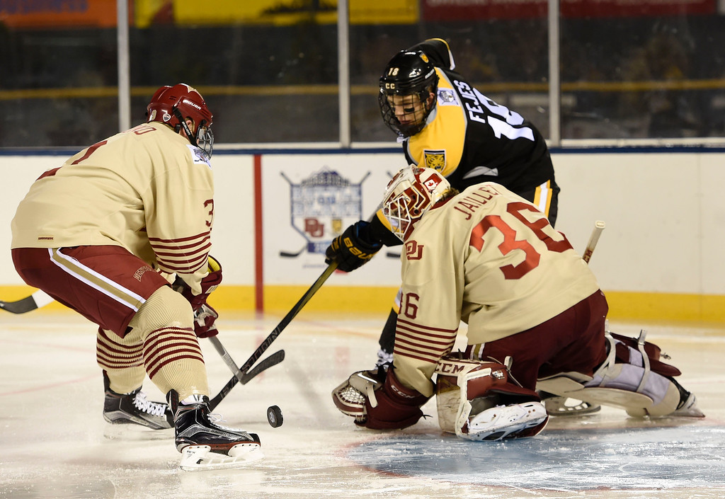. Colorado College Tigers forward Hunter Fejes (18) goes after the puck with Denver Pioneers defenseman Tariq Hammond (3) and Denver Pioneers goalie Tanner Jaillet (36) during the second period in the Battle On Blake February 20, 2016 at Coors Field.  (Photo By John Leyba/The Denver Post)