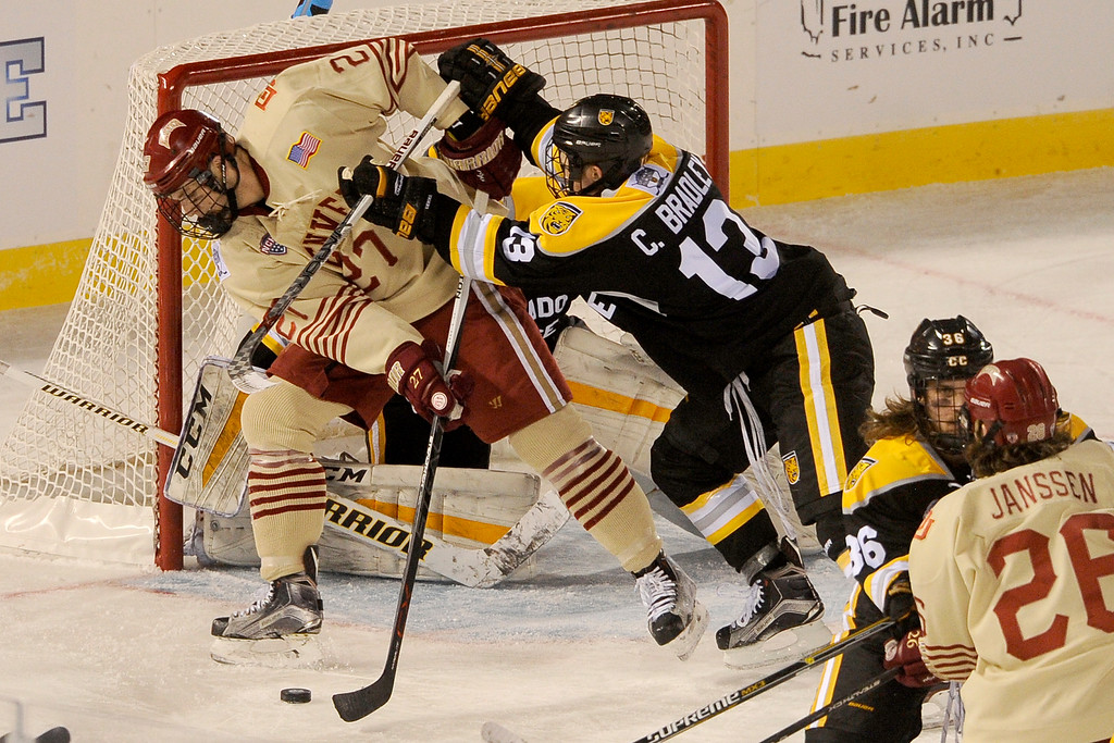 . Cody Bradley (13) of Colorado College cross checks Quentin Shore (27) of the University of Denver as he attempts to make a back handed shot in front of the Colorado net during the second period at Coors Field in Denver, Colorado on February 20, 2016. (Photo by Seth McConnell/The Denver Post)