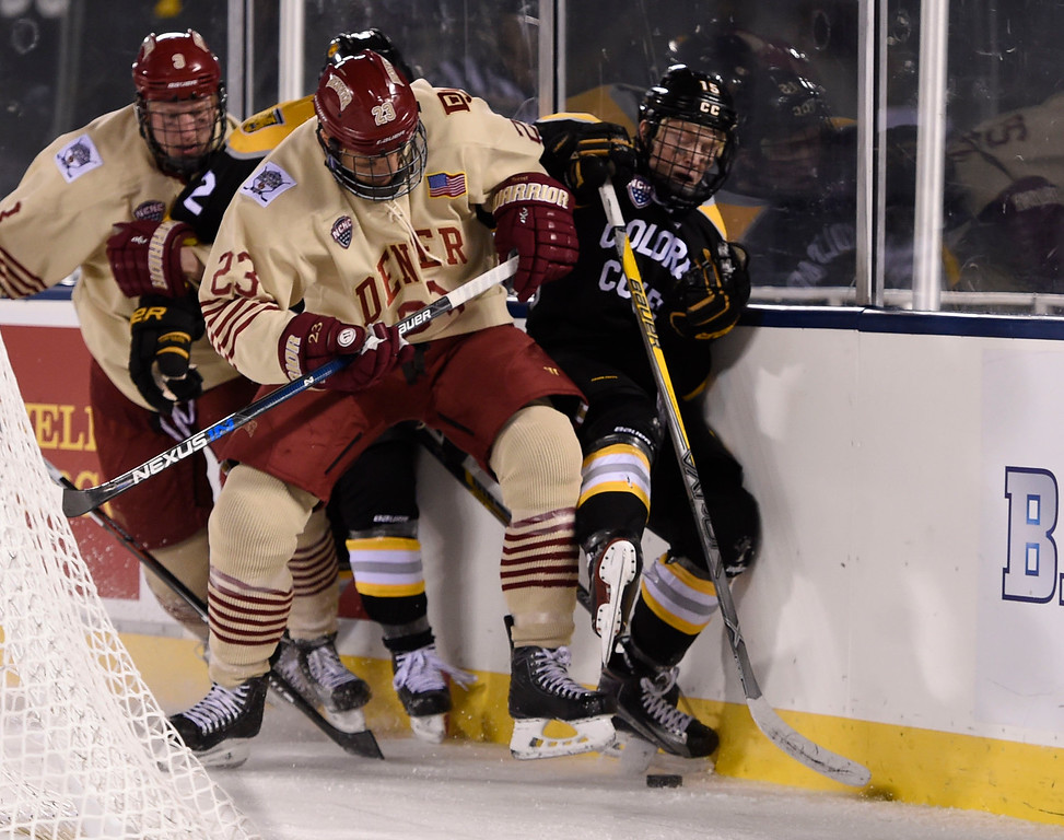 . Denver Pioneers forward Matt Marcinew (23) pins Colorado College Tigers forward Mason Bergh (15) up against the boards as the puck comes loose in the second period during the Battle On Blake February 20, 2016 at Coors Field.  (Photo By John Leyba/The Denver Post)