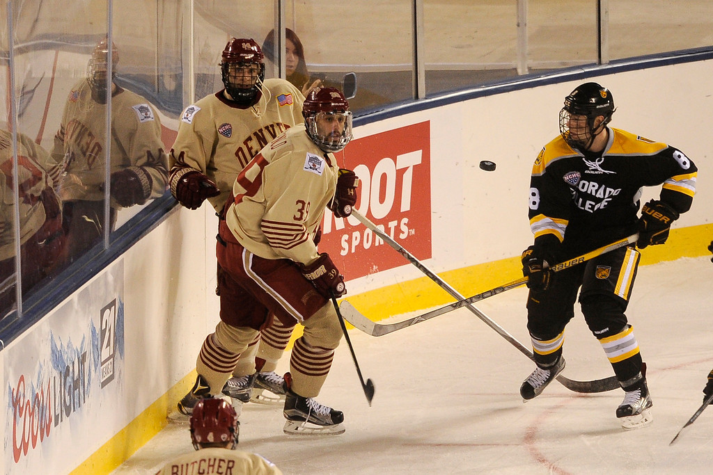 . Grant Arnold (39) of the University of Denver and Luc Gerdes (8) of Colorado College watch as a puck flies between them during the third period at Coors Field in Denver, Colorado on February 20, 2016. (Photo by Seth McConnell/The Denver Post)